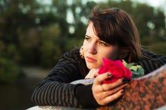 Traurige junge Frau mit einer Rose Stockfoto