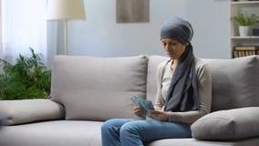 Traurige junge Frau mit Krebs, der Geld, Versicherung, teure Behandlung zählt stock video