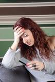 Traurige junge Frau mit Kreditkarte und Laptop Lizenzfreie Stockfotos