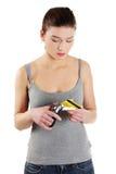 Traurige junge Frau muss ihre Kreditkarte zerstören Stockbild