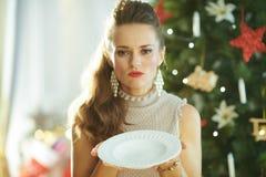 Traurige junge Frau nahe dem Weihnachtsbaum, der leeren großen Teller hält stockbild
