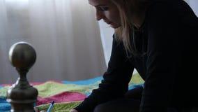 Traurige junge Frau schreibt in ihr Tagebuch beim Sitzen auf einem Bett jugendliche Erfahrungen Langsame Bewegung stock video
