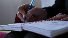 Traurige junge Frau schreibt in ihr Tagebuch beim Sitzen auf einem Bett jugendliche Erfahrungen Langsame Bewegung stock video footage