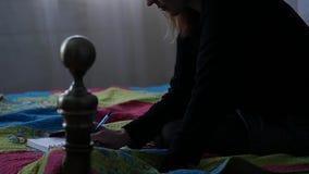 Traurige junge Frau schreibt in ihre Zeitschrift beim Sitzen auf einem Bett jugendliche Erfahrungen Langsame Bewegung stock video