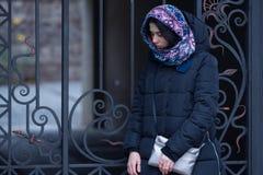 Traurige junge Frau steht nahe einem Weinleseeisentor Stockfotografie