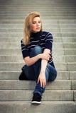 Traurige junge Modefrau, die auf den Schritten sitzt Lizenzfreies Stockbild