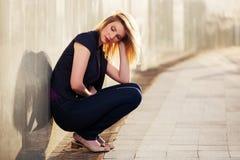 Traurige junge Modefrau, die an der Wand sitzt Stockbild