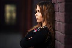 Traurige junge Modefrau im schwarzen Kleid an der Backsteinmauer Stockfoto