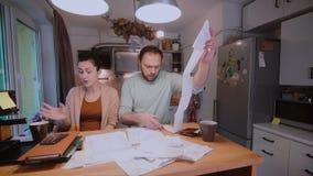 Traurige junge Paare, welche die Wechsel einlösen Mann und Frau, die in der Küche sitzen und Kontrollen und Konten sortieren stock footage