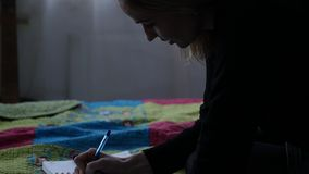 Traurige junge Studentin schreibt in ihre Zeitschrift beim Sitzen auf einem Bett jugendliche Erfahrungen Langsame Bewegung stock video footage