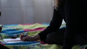 Traurige junge Studentin schreibt in ihre Zeitschrift beim Sitzen auf einem Bett jugendliche Erfahrungen Langsame Bewegung stock video