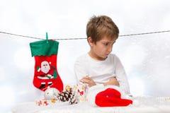 traurige Jungen mit Weihnachtsdekorationen Stockbilder