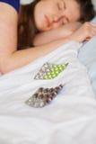 Traurige kaukasische Frau, die mit Pillen schläft Stockfotografie