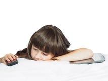 Traurige kaukasische Kinderkindermädchenschwester, die auf dem Bett mit dem Handy- und Tabletten-PC lokalisiert liegt Stockbild
