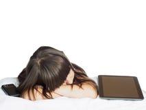Traurige kaukasische Kinderkindermädchenschwester, die auf dem Bett mit dem Handy- und Tabletten-PC lokalisiert liegt Lizenzfreies Stockbild