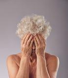 Traurige ältere Frau, die ihr Gesicht bedeckt Lizenzfreies Stockfoto
