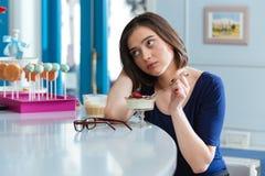 Traurige müde Frau, die Nachtisch isst und Latte im Café trinkt Lizenzfreie Stockbilder