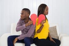 Traurige Paare, die rotes defektes Herz halten Lizenzfreies Stockbild