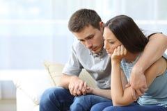 Traurige Paare, die sich zu Hause trösten stockfoto