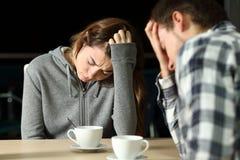 Traurige Paare von Jugendlichen in einer Stange lizenzfreie stockfotos
