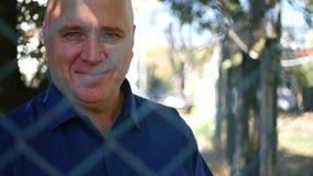 Traurige Personen-Rückseite eines metallischen Zauns Look zur Kamera und des Lächelns überzeugt stock footage