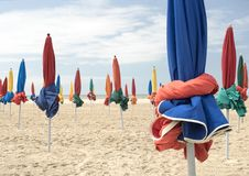 Traurige Regenschirme auf dem Strand stockbild