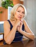 Traurige reife Frau, die nahe Tabelle sitzt Lizenzfreie Stockbilder