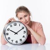 Traurige schöne junge blonde Frau, die auf einer Uhr sich lehnt Stockfotografie