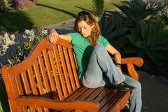 Traurige schauende Frau, die am Park sitzt Lizenzfreie Stockbilder