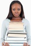 Traurige schauende junge Frau mit Stapel der Bücher Lizenzfreie Stockbilder