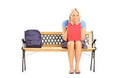Traurige Studentin, die auf einer Holzbank sitzt Stockbild