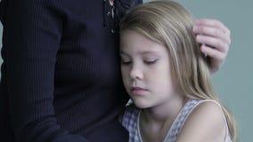 Traurige Tochter, die zu Hause seine Mutter umarmt stock footage