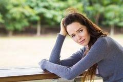 Traurige, umgekippte und besorgte Frau, die draußen sitzt Lizenzfreie Stockfotos