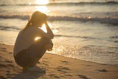 Traurige und allein junge Frau am Strand lizenzfreie stockbilder