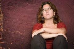 Traurige und deprimierte Frau, die auf dem Boden sitzt Lizenzfreie Stockfotos