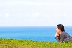 Traurige und deprimierte Frau, die im grünen Gras liegt Lizenzfreies Stockfoto