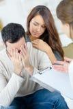 Traurige und deprimierte Paare der Psychotherapie Stockfotografie