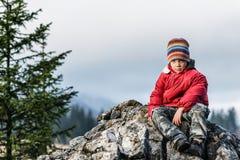 Traurige und einsame Stellung des Jungen auf einer Klippe Stockfotografie