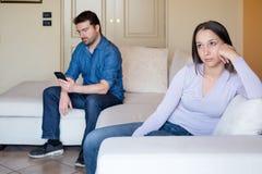 Traurige und gebohrte junge Frau, die auf dem Sofa sitzt Stockbild