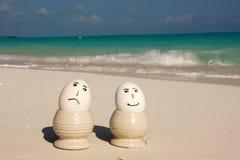 Traurige und glückliche Strandeier lizenzfreie stockfotografie