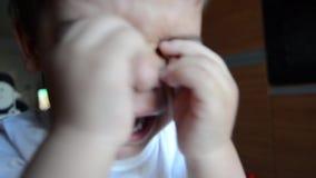 Traurige und müde zwei Jahre alte Junge, die seine Augen schreien und reiben stock footage