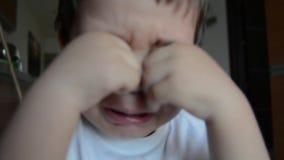 Traurige und müde zwei Jahre alte Junge, die seine Augen schreien und reiben stock video footage