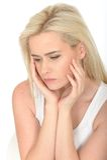 Traurige unglückliche durchdachte junge Frau, die besorgt oder deprimiert schaut Lizenzfreies Stockbild