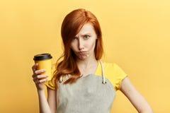 Traurige unglückliche Verkäuferin mit einem Tasse Kaffee stockfotografie