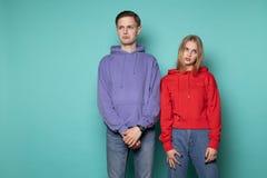 Traurige ungl?ckliche Paare, sch?nes blondes M?dchen im roten Hoodie und h?bscher Junge im purpurroten Hoodie lizenzfreies stockbild