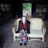 Traurige weiß-gesichtige Dame in einem geflochtenen Stuhl lizenzfreies stockbild