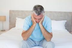 Trauriger älterer Mann auf Bett Stockbilder