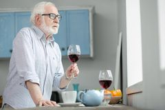 Trauriger älterer Mann, der im Fenster schaut stockbilder