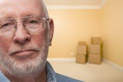 Trauriger älterer Mann im leeren Raum mit Kästen Stockbild