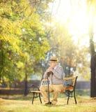 Trauriger älterer Mann mit dem Stock, der auf Bank in einem Park sitzt Lizenzfreies Stockbild